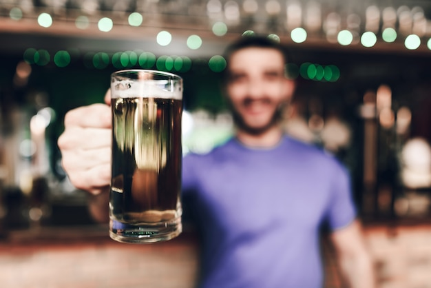 Close up barmen holding glass of beer in bar