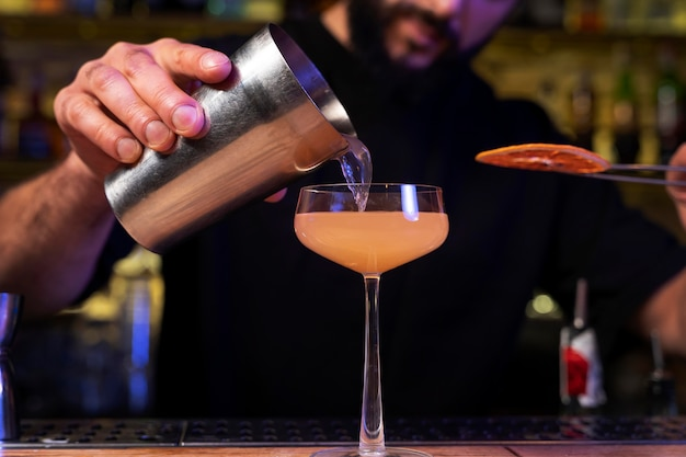 Close up on bartender and cocktail shaker
