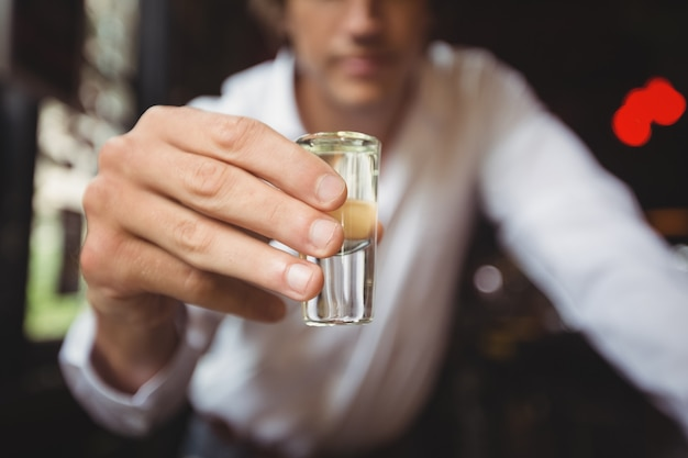 Close-up of bartender holding tequila shot glass at bar counter