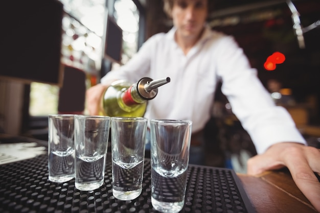 Close-up of bartender pouring tequila in shot glasses