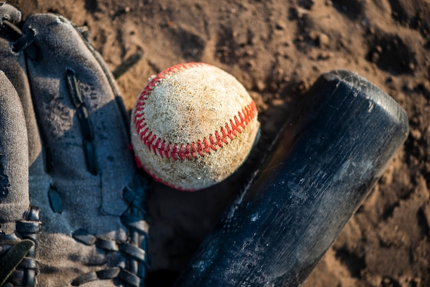 Close-up of baseball and bat in dirt