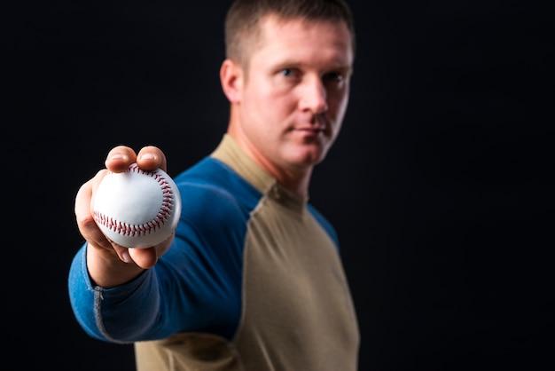 Close-up of baseball held by man