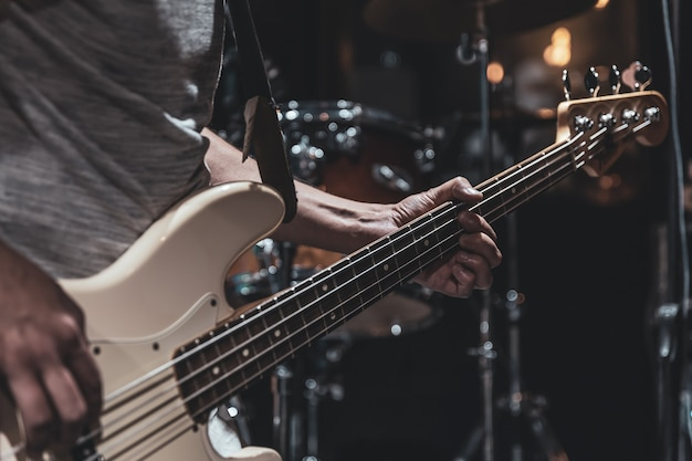 Close up of bass guitar on blurred dark background copy space.