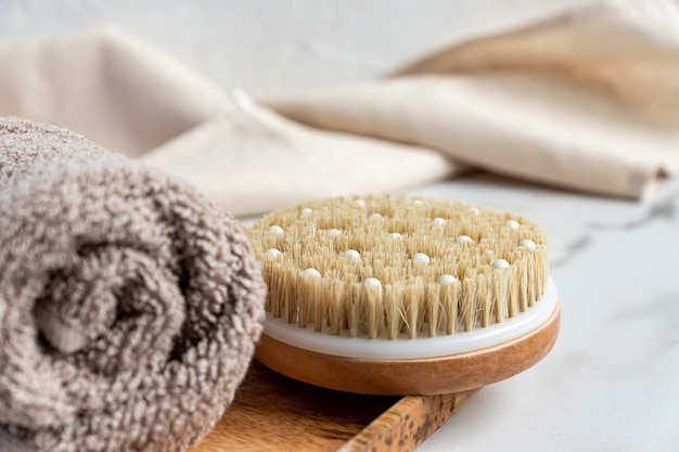 Close up of a bath bamboo brush for dry massage and cotton towel on a wooden tray on marble