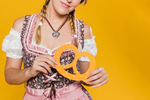 Крупный план баварской девушки с бумажным кренделем