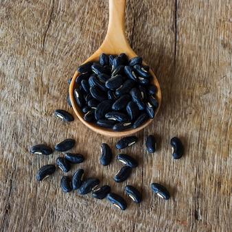 나무 테이블에 콩 씨앗 숟가락을 닫습니다