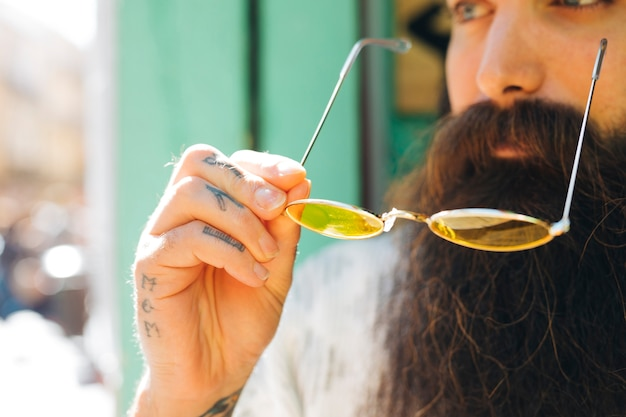 Close-up of beard man holding yellow eyeglasses in sunlight
