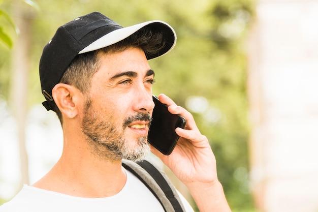 Close-up of beard man wearing cap talking on mobile phone