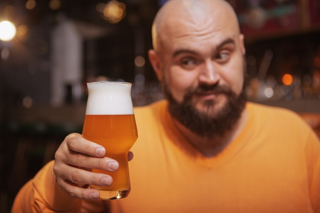 Close up of a bearded cheerful man looking at the glass of beer in his hand, enjoying drinking at the bar