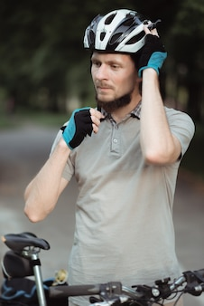 Close up of bearded delivery man wearing helmet while standing with bicycle outdoors, ready to ride a bicycle
