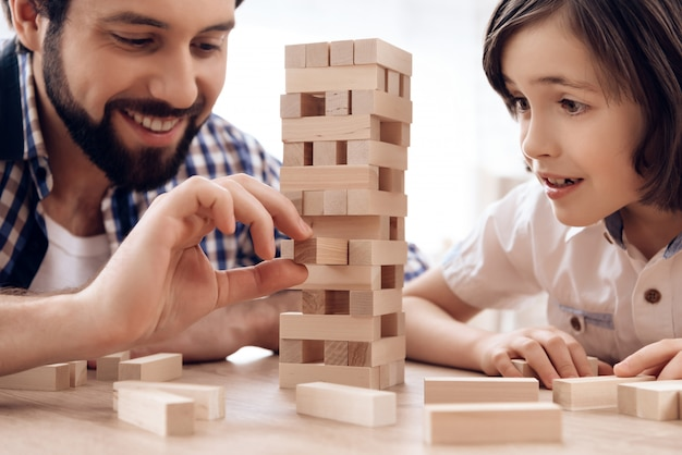 Close up. bearded father with small son plays jenga at home.