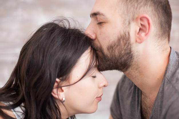 Close up of bearded husband kissing his wife forehead in the morning.