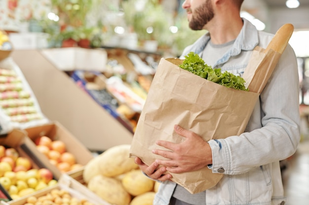 Close-up of bearded man in denim jacket carrying full paper bag of fresh products at food market
