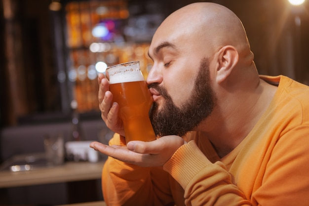 Close up of a bearded man kissing glass of delicious beer at the pub