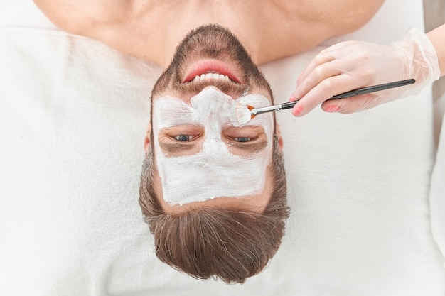 Close up bearded young man is relaxing while cosmetologist is spreading white clay on his face