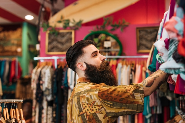 Close-up of bearded young man looking at clothes hanging on rail