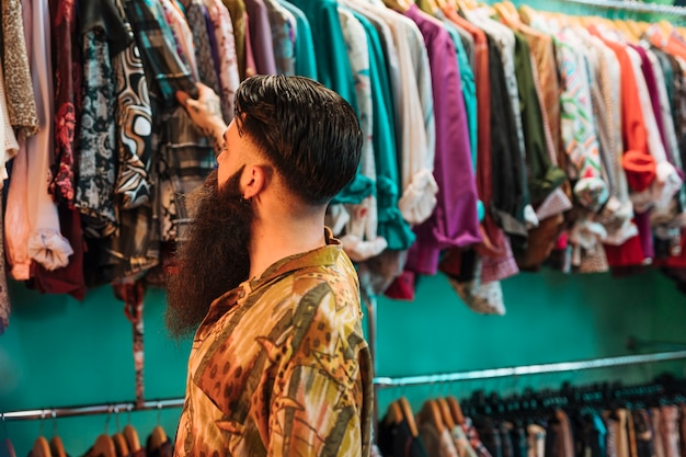 Close-up of bearded young man looking at shirts hanging on rail in the shop