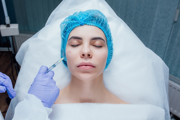Close up of beautician expert's hands injecting botox in female forehead