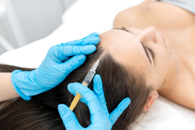 Close-up, the beautician makes injections of vitamins into the scalp for strengthening the hair.
