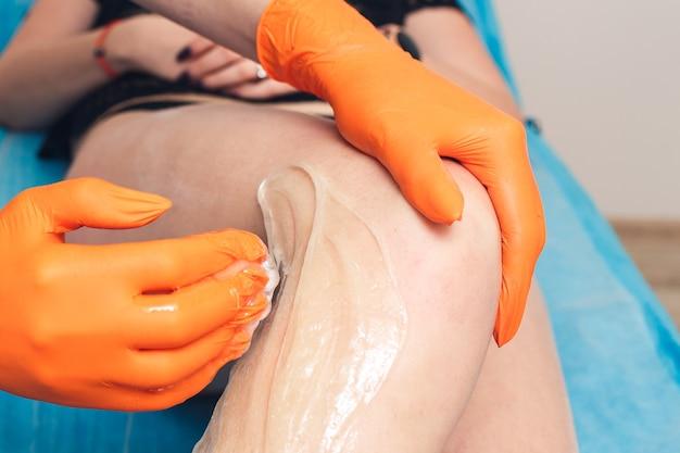 Косметолог крупным планом делает девушке на ноге шугаринг.