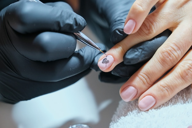 Close-up beautician painting art design on nails.