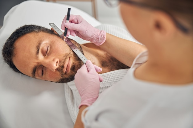 Close up of beautician in sterile gloves placing ruler on male cheek and drawing straight line with white pencil