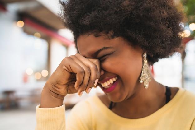 Primo piano di una bella donna latina afroamericana sorridente e trascorrere del bel tempo presso la caffetteria.
