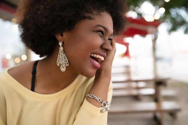 Close-up of a beautiful afro american latin woman smiling and spending nice time at the coffee shop.