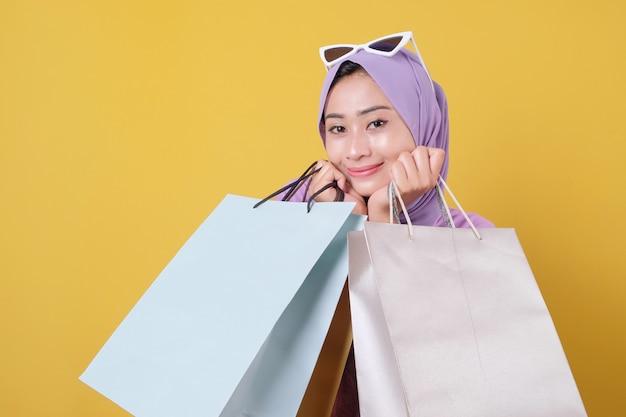 Close up beautiful asian wearing glasses shopaholic women holding shopping bags