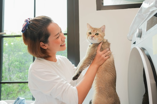 Close up beautiful asian woman smile and raising the charming adorable cat during working household chores in wash room for cat lover and lifestyle people concept
