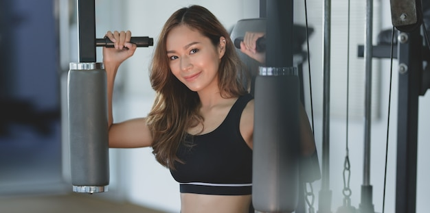 Close-up of beautiful asian woman with tan and slim body exercise on machine