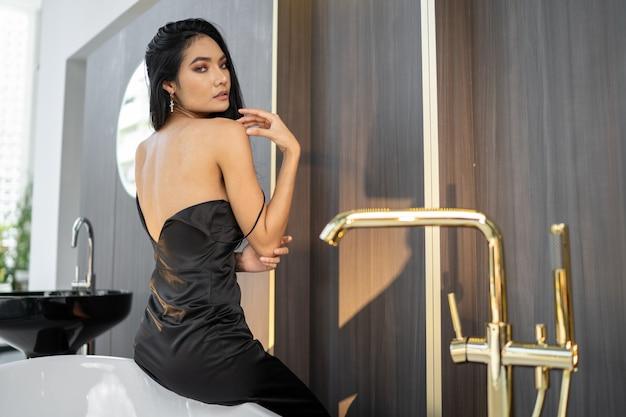 クローズアップバスタブでシャワーを浴びている美しいアジアの女性と、バスルームでシャボン玉を弾いている彼女はリラックスした気分です。