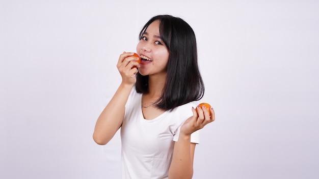 白い表面に分離されたトマトで美しいアジアの女性をクローズアップ