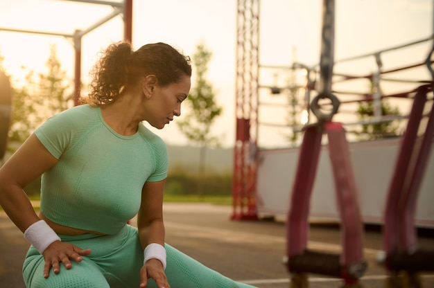Close-up of beautiful athlete woman doing warm-up, warming up before training outdoors in summer sportsground, kneading and stretching leg muscles. out of focus of suspension straps on the foreground