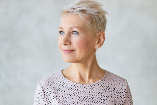 Close up beautiful attractive middle aged european lady with stylish haircut and neat make up looking away with confident smile posing isolated against marbled wall