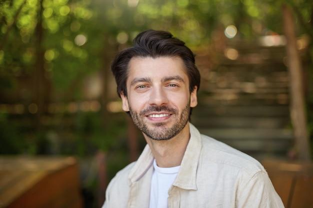 Primo piano di bello maschio barbuto con capelli scuri in posa su green ciy park in giornata di sole, guardando con un sorriso affascinante e sincero