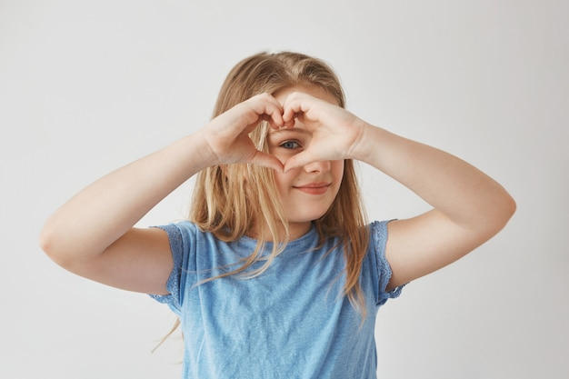 Close up of beautiful blonde girl making heart with hands, looking through it , posing for photo with smile and happy expression.