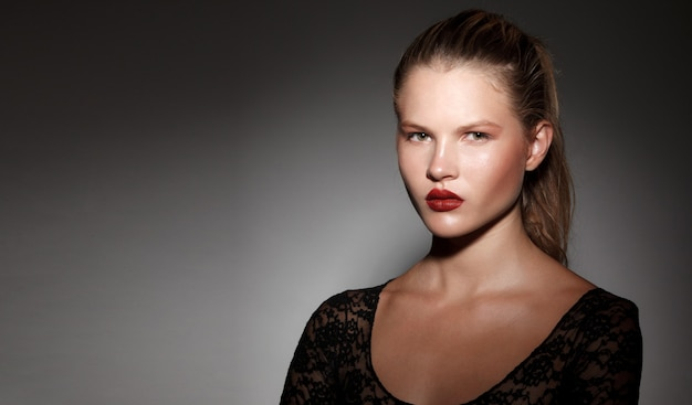 Close up of a beautiful blonde girl with hair gathered in a ponytail with red lips on dark background. copy space.