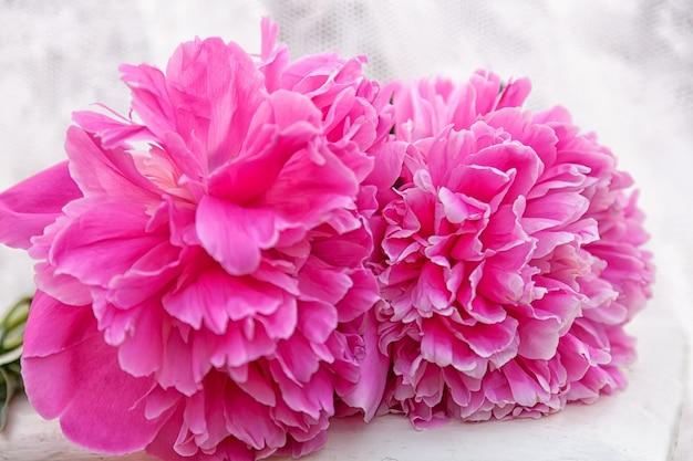 Крупным планом красивый букет с крупными цветами пионов, только что срезанный, лежит на белом табурете