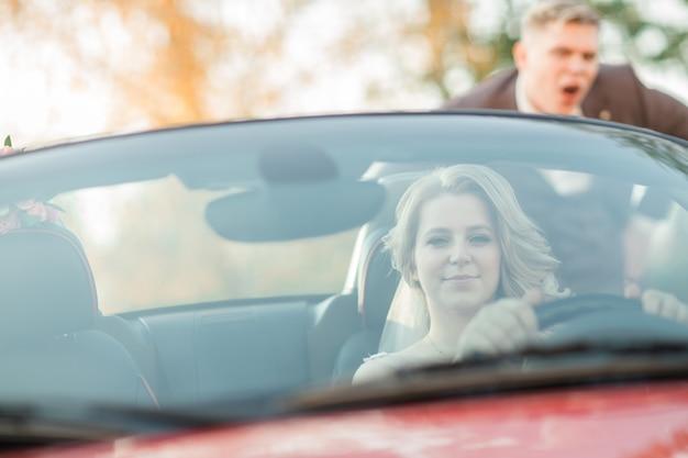 Закройте вверх. красивая невеста сидит за рулем автомобиля. фото с копией пространства