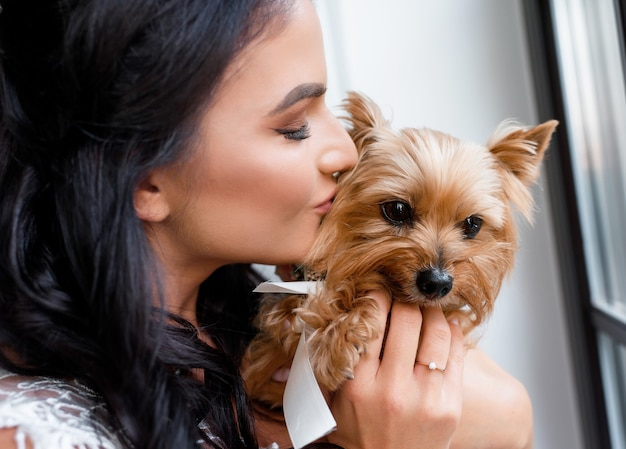 Close up of beautiful brunette bride holds in her arms and kisses a yorkshire terrier