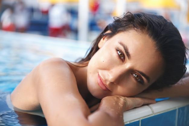 Primo piano di bella donna bruna con abbronzatura estiva, appoggiato a bordo piscina e sorridendo alla telecamera.