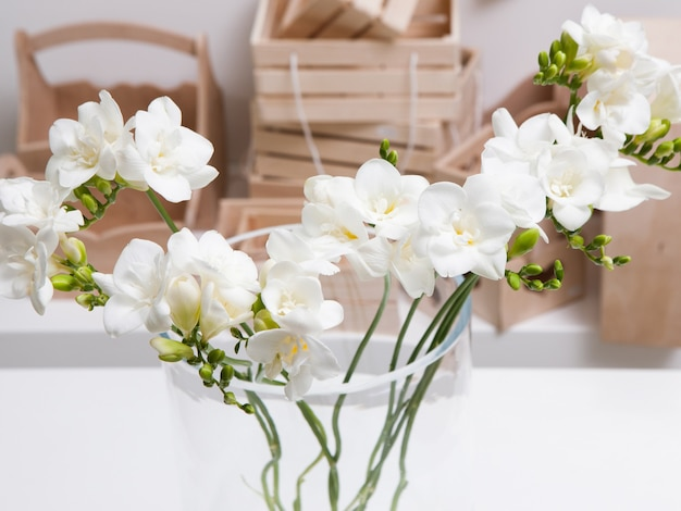 Close up beautiful bunch of white orchid in glass vase on table and wooden boxes background. floristics workshop, floral arrangement for presents, tenderness in interior and decoration concept