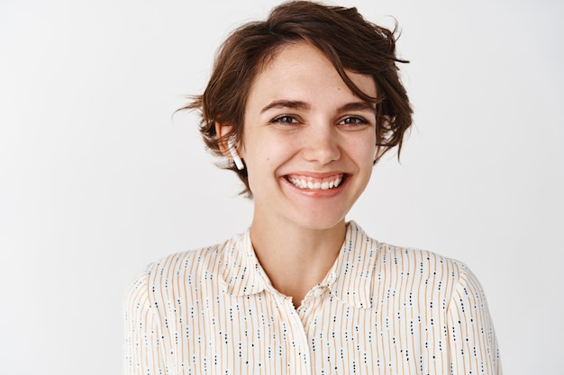 Close-up of beautiful candid woman smiling and looking happy, listening music or podcast in wireless earphones, wearing headphones on white wall