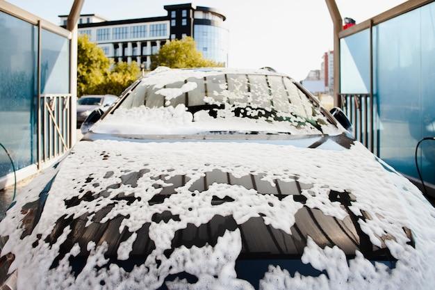 Крупным планом красивый автомобиль покрытый мыльной пеной