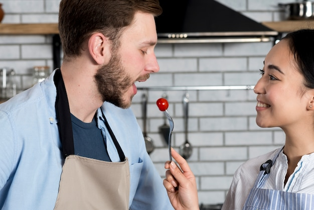 Close-up of beautiful couple feeding tomato in kitchen