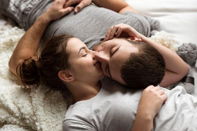クローズアップ美しいカップルがベッドでキス