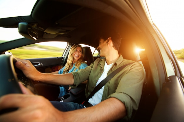 Close up beautiful couple laughing in car on road trip