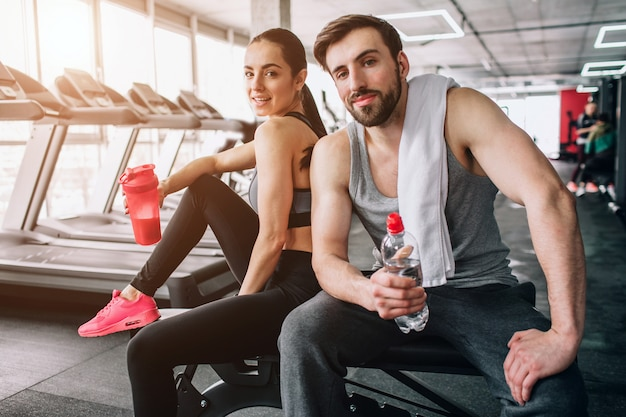 Close up of a beautiful couple sitting on the sport bench and posing. also they are drinking water from their bottles and having rest after hard workout.