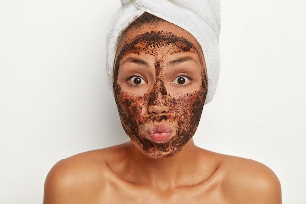 Close up of beautiful dark skinned girl applies facial scrub mask for good effect, chooses appropriate beauty product for her type of skin, keeps lips rounded, wears towel on head, has morning routine